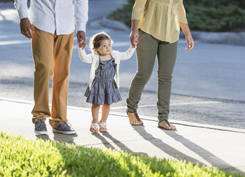 Hispanic toddler walking with parents