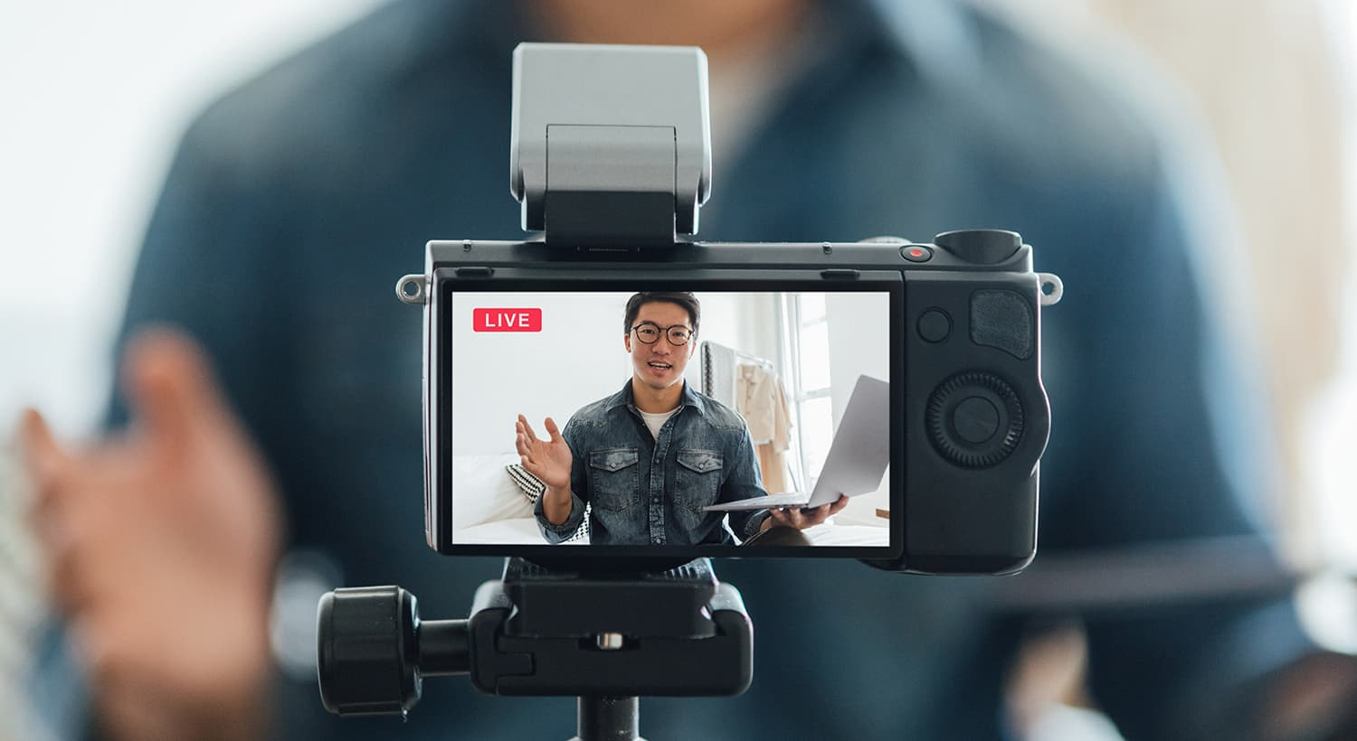 Copped shot of confident real estate agent talking while filming through video camera for vlogging at home.